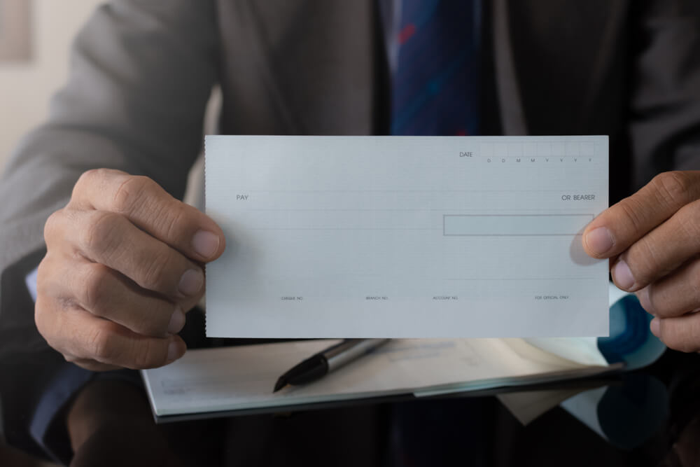 Businessman in Suit Hand Holding and Showing Blank Cheque