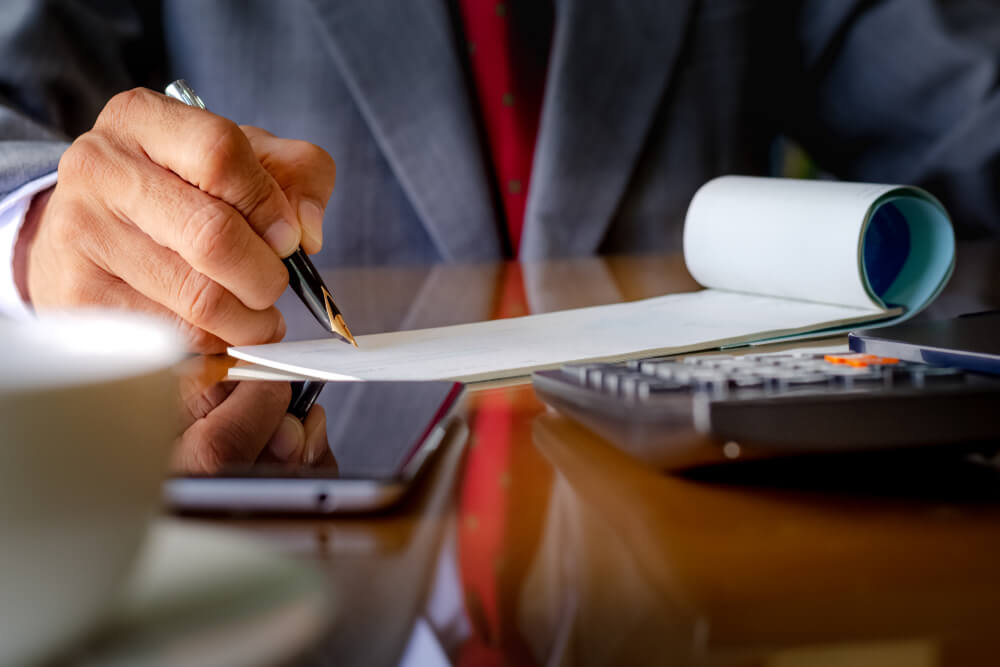 Business Man in Grey Suit Signing Blank Check Book