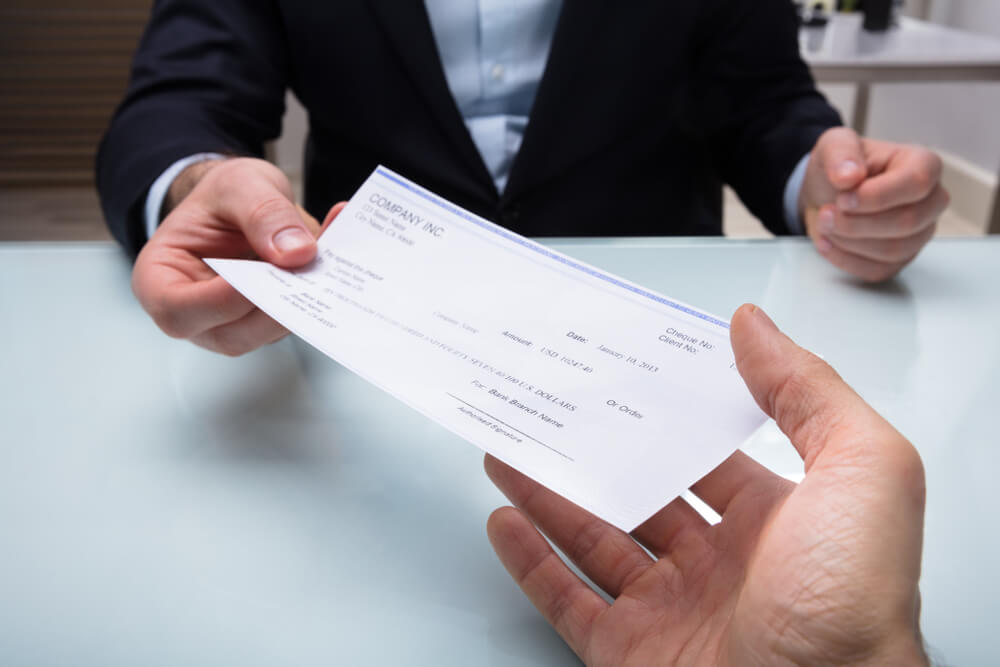 Close-up Of A Businessman's Hand Giving Cheque