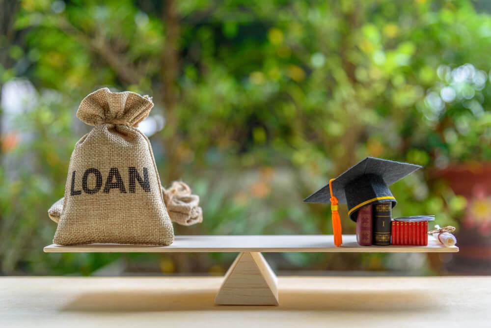 Mortarboard, Loan Bag on Balance Scale Student Loan Disbursement Concept