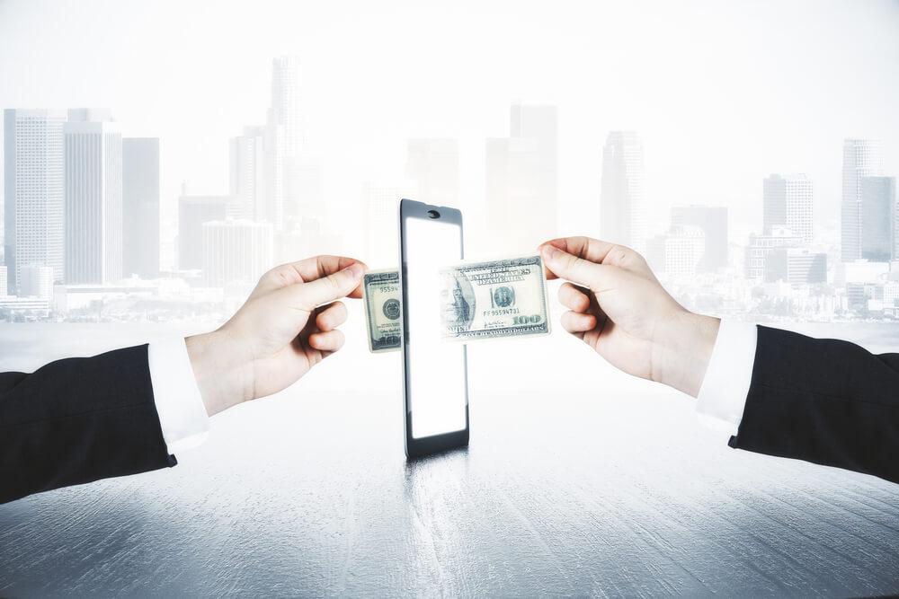 A Man Passes Another Man Money Through Smartphone