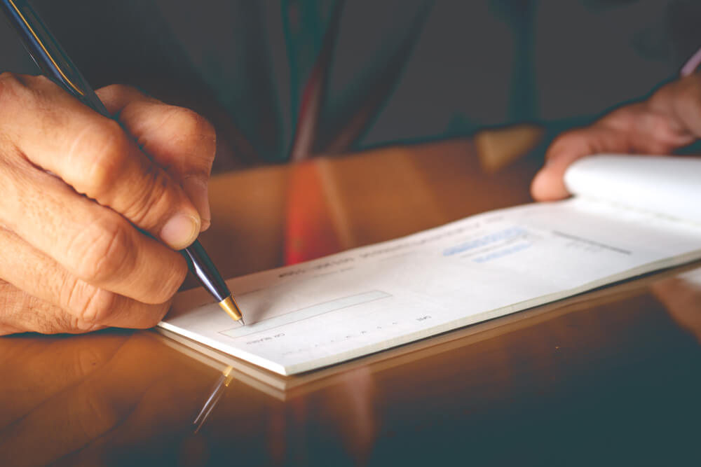 Closeup of Businessman Hand Writing and Signing Check on the Table at Office