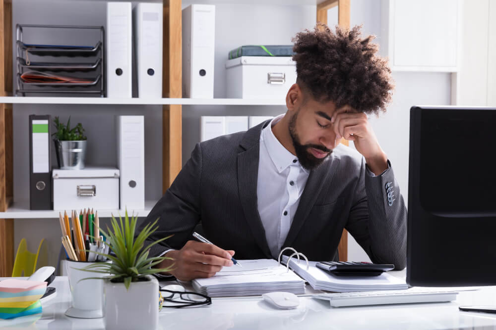 Unhappy Young Businessman Calculating Bill in Office