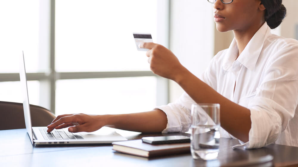 Faceless African American Woman Making Wire Transfers Online Using Her Credit Card