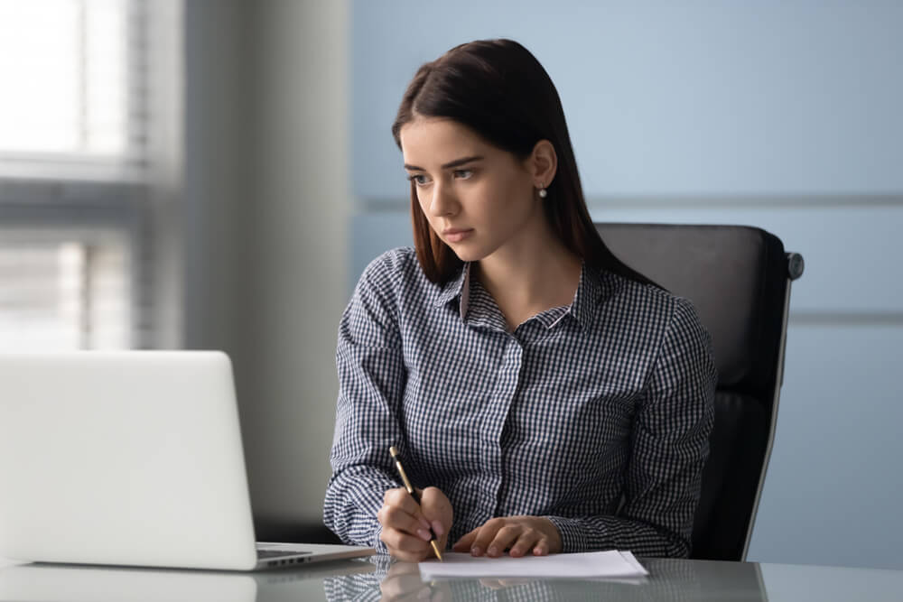 Concentrated Young Businesswoman Writingon Paper Watching Business Webinar on Laptop