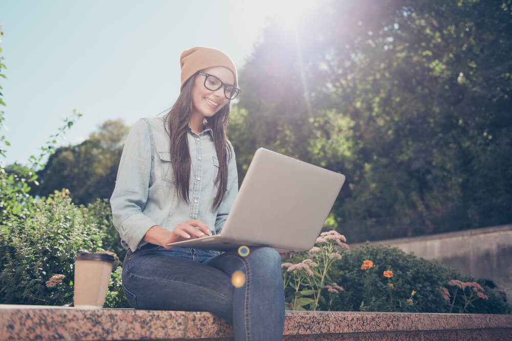 Happy Hipster Young Woman Working on Laptop in the Park