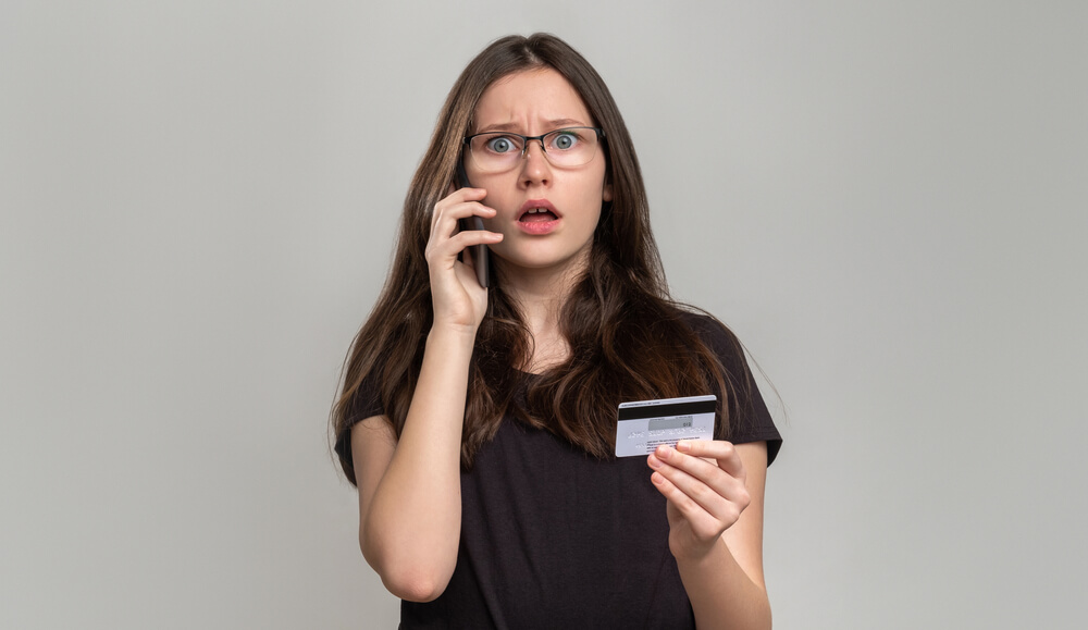 Shocked Woman Checking Credit Card Balance on Phone Isolated on Gray.