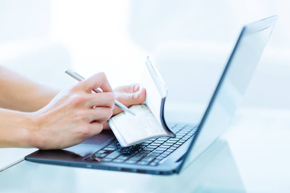 Closeup of a Hands Writing a Personal Bank Cheque Using a Pen While Working on a Laptop Computer.