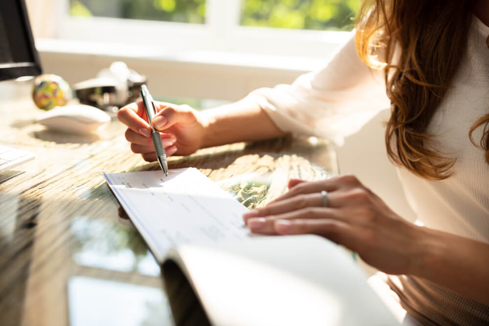 Businesswoman's Hand Signing Cheque on Wooden Desk