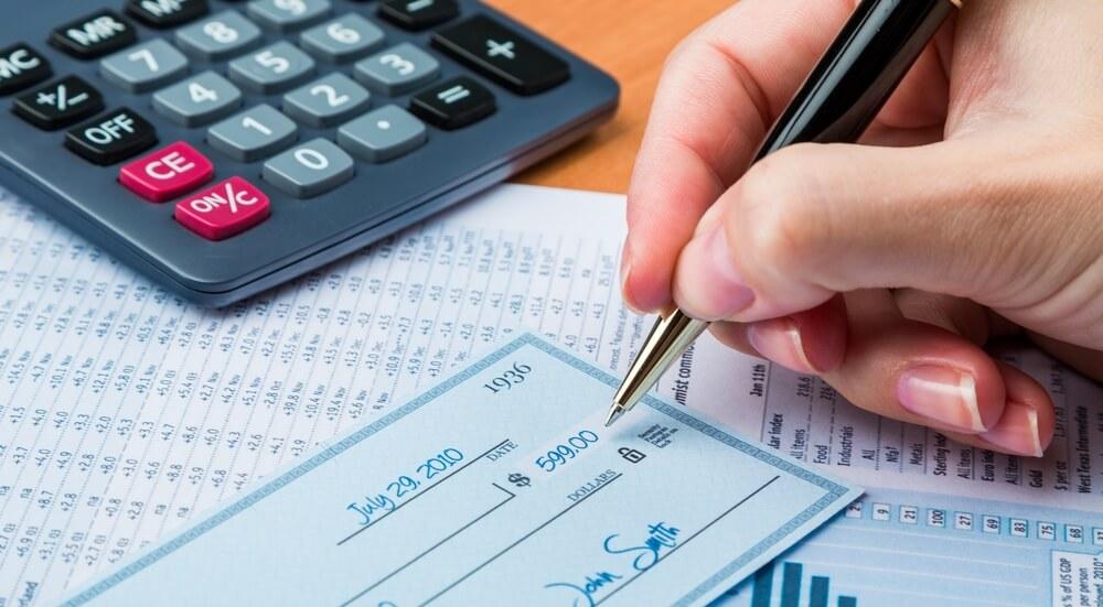 Person Writing a Check Next to a Calculator